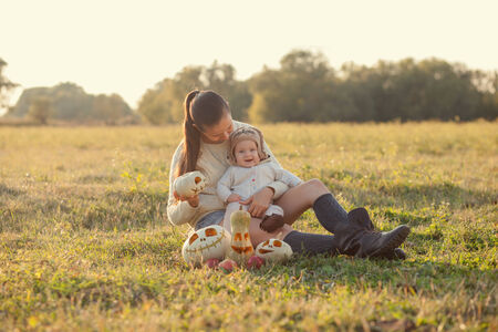 Mother and baby have fun with pumpkins photo