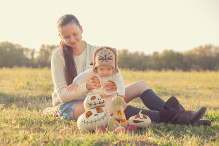 Mother and baby have fun during pumpkin harvest photo