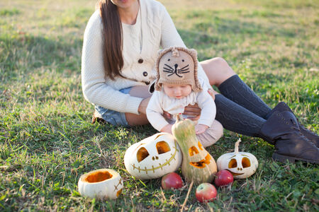 Family sitting on grass during pumpkin harvest photo