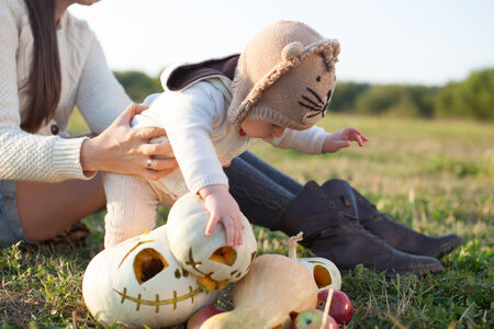 Baby in arms playing with pumpkins photo