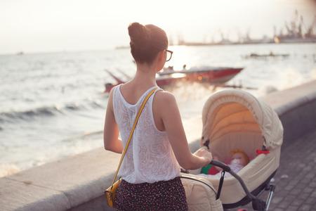 niño empujando: Madre paseando con el recién nacido