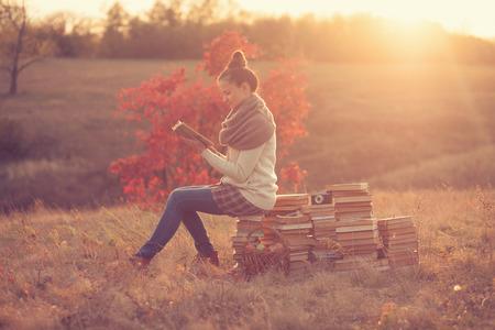 Hipster meisje lezen bij zonsondergang