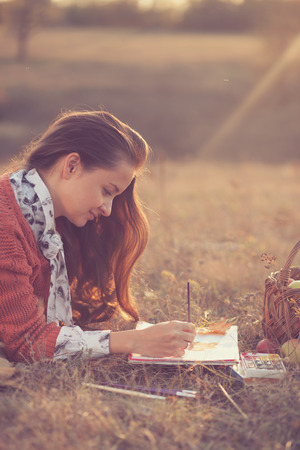 Lying Hipster styled woman drawing