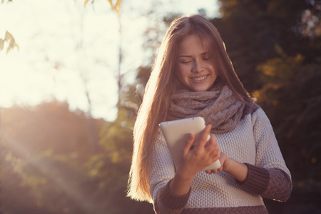 Smiling teen girl posing with tablet photo
