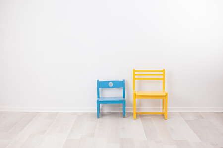 Two vintage child chairs on white wall Reklamní fotografie - 34596566