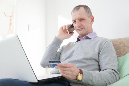 Volwassen man het lezen van een credit card nummer tijdens telefoongesprek