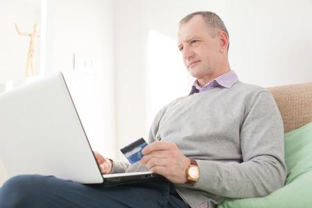 Volwassen man die online kopen Stockfoto