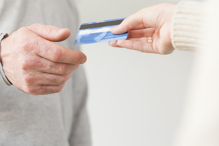 Female hand giving a plastic card to senior male hand Stockfoto