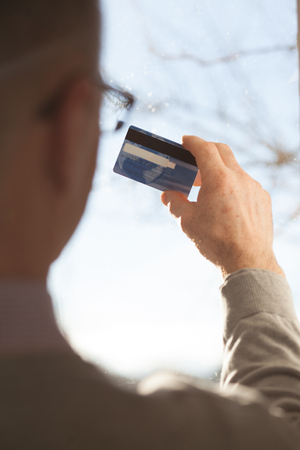 Senior male hands holding a plastic card photo