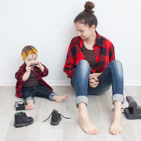same: Mother and baby in red checkered shirts and jeans Stock Photo