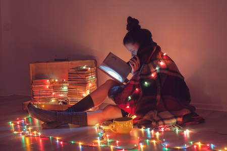 introvert: girl reading a book under blanket at home in cold weather