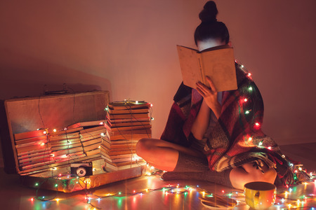 teenage girl: girl reading a book under blanket at home in cold weather
