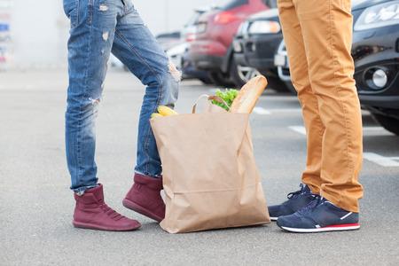 Páry nohou a nákupní taška s jídlem