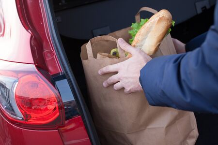 car trunk: Mans hands loading a shopping bag in car trunk Stock Photo