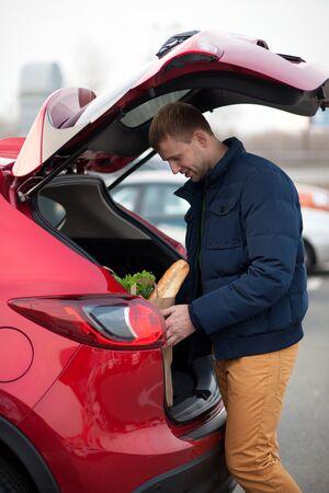 car trunk: Man loading a shopping bag in car trunk