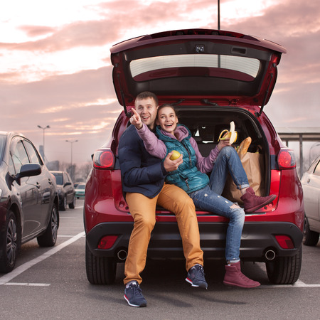 drives: Happy couple sitting at car trunk after shopping