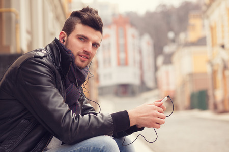 sexy headphones: Stylish guy with smartphone in the city