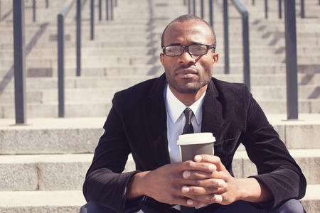 office attire: black bussinesman sitting with coffee during a lunch Stock Photo