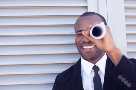 thru: black man searching thru paper spyglass