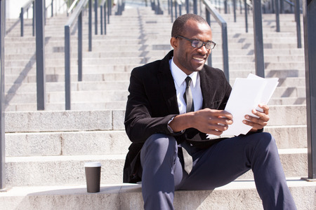 office attire: happy black businessman sitting with coffee and documents handling
