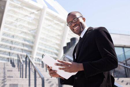 working attire: happy black businessman documents handling Stock Photo