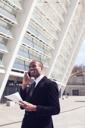 working attire: black businessman have phone conversation outdoors