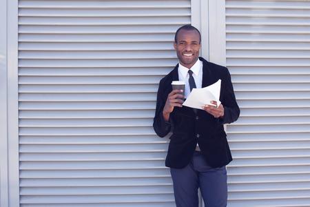 handling: stylish black man documents handling outdoors Stock Photo