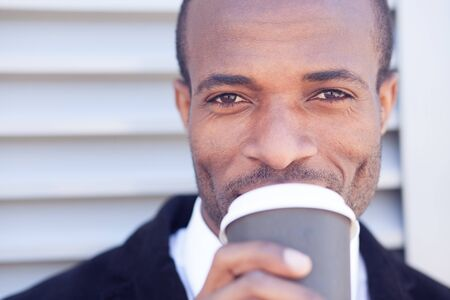 office attire: trendy black man have coffee break outdoors