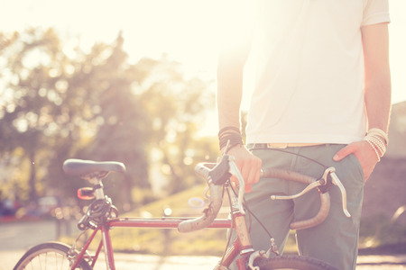 Stylish guy holding vintage race bike Archivio Fotografico