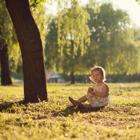 under tree: toddler sitting under the tree