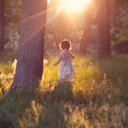 mignonne petite fille: Marche bébé dans les feux de coucher du soleil Banque d'images