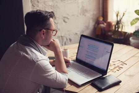 estilo urbano: El hombre con estilo usando la computadora portátil en la oficina Foto de archivo