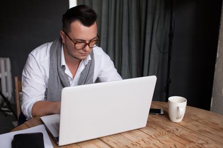 Stijlvolle man met behulp van laptop in het kantoor
