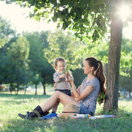 happy mom: Mother showing green leaf to toddler