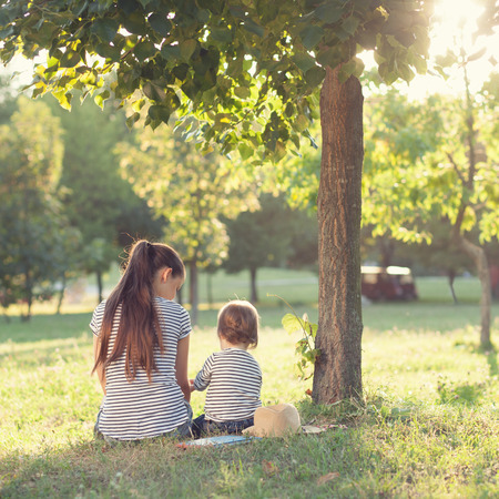 happy mom: Mother and toddler sitting under the tree during summer leisure