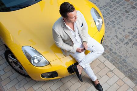Stilvoller junger Mann posiert mit Sport Auto Standard-Bild