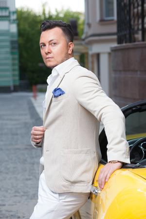 rich life: Stylish young man posing near sport car