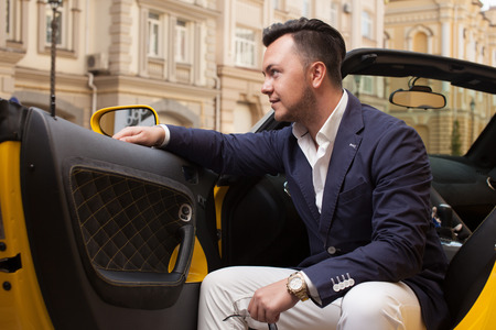 Stylish man sitting in sport car Foto de archivo