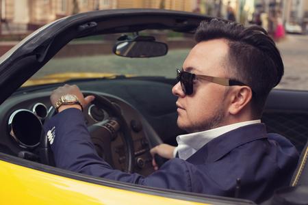 Stilvoller Mann sitzt im Sport Auto Standard-Bild - 45043465