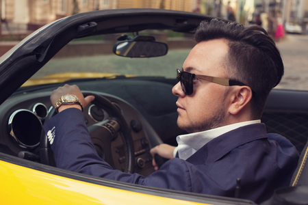 Stylish man sitting in sport car Imagens