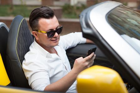 chofer: Hombre controlador que usa smartphone en el coche