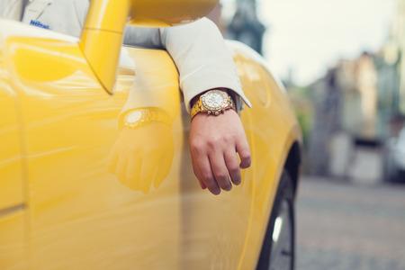차에 황금 시계 남자 손의 근접 촬영
