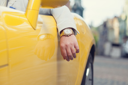 Closeup of man hand with golden watch in car Stockfoto