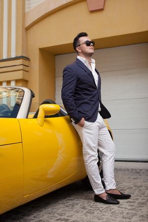 Stylový muž pózuje s kabriolet sportcar