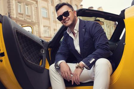 Stylish man sitting in sport car Standard-Bild