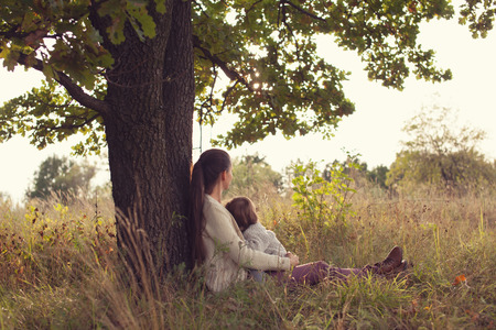 breastfeeding: Mother and toddler girl have rest outdoors Stock Photo