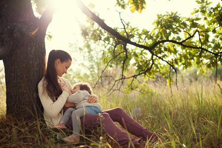 jonge moeder voeden peuter buiten