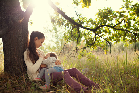 young mother feeding toddler outdoors