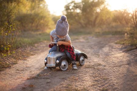 juguetes antiguos: Ni�o que conduce el coche del juguete al aire libre Foto de archivo