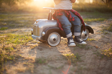 Little racer and tiny race car Archivio Fotografico